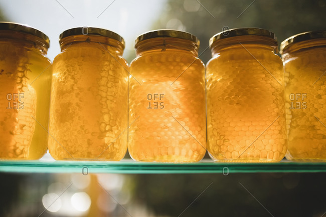 Close-up of honey and comb in glass jars on shelf at supermarket