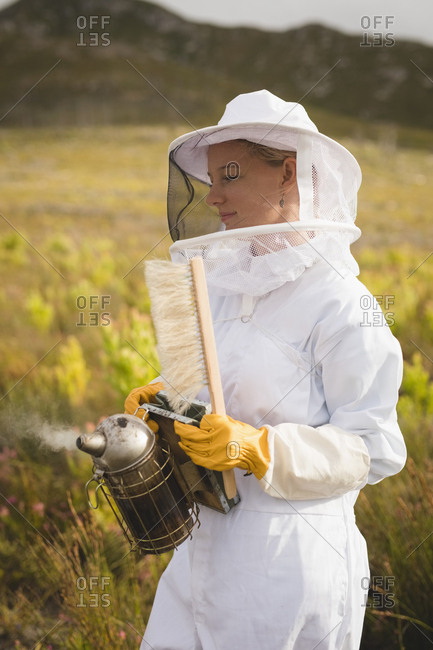 Female beekeeper holding bee smoker and brush on farm