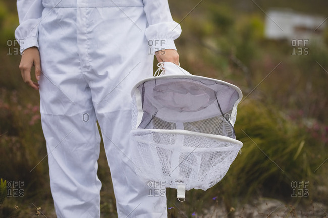 Midsection of male beekeeper holding protective hat at apiary