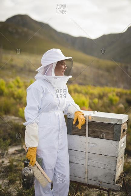 Female beekeeper standing by artificial beehive on field