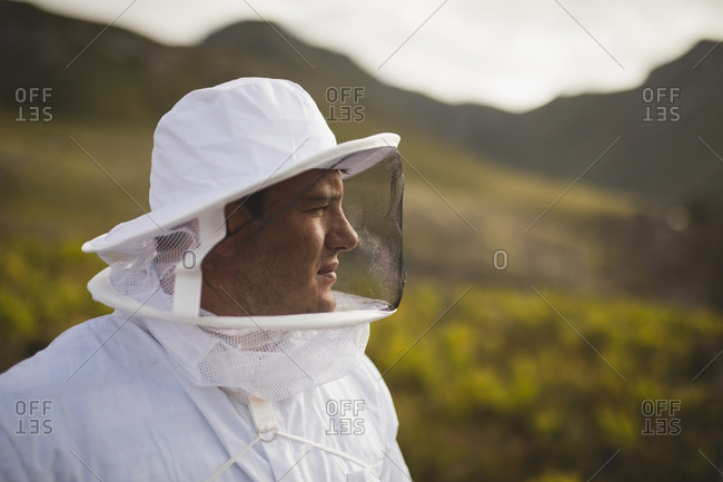 Close-up of thoughtful man wearing bee suit at apiary