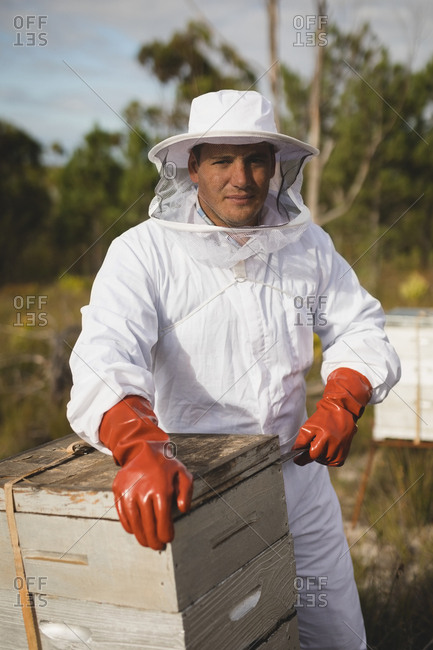Portrait of confident male beekeeper working on beehive at apiary