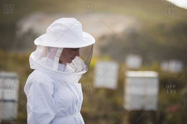 Side view of female apiarist wearing bee suit at apiary
