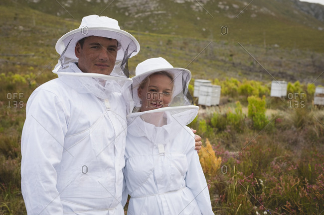 Portrait of confident male and female beekeepers at apiary
