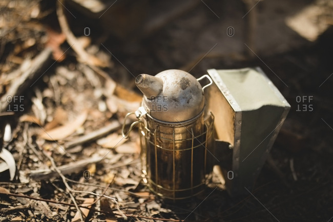 Close-up of bee smoker on ground at apiary