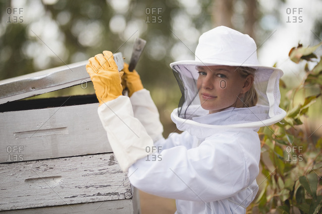 Portrait of female beekeeper opening honeycomb at apiary