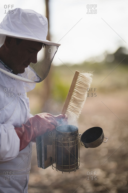Side view of male beekeeper holding bee smoker and brush at apiary