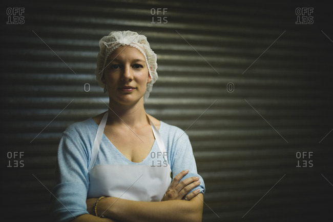 Portrait of female beekeeper wearing protective headdress at beekeeping factory