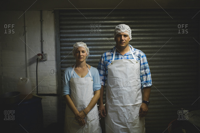 Portrait of male and female workers standing in beekeeping factory