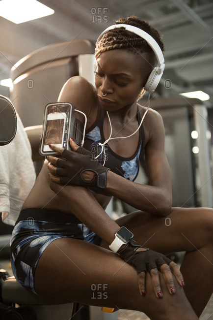 Fit woman using smartphone in armband at gym
