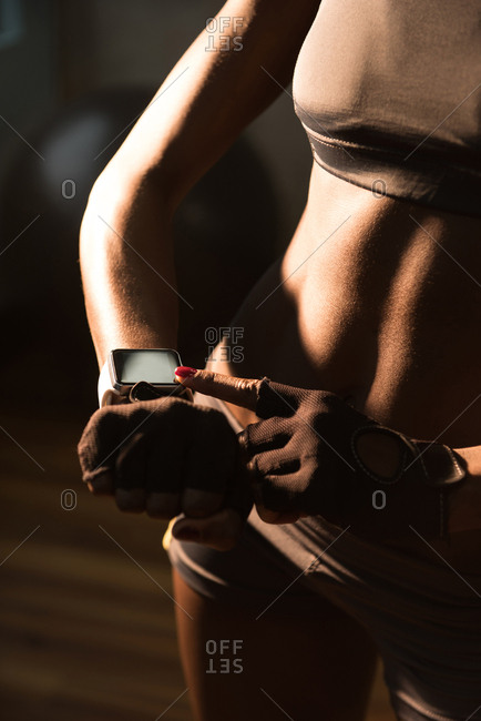 Mid-section of fit woman using smart watch in the gym