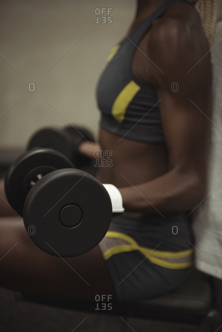 Mid-section of fit woman exercising with dumbbells in the gym