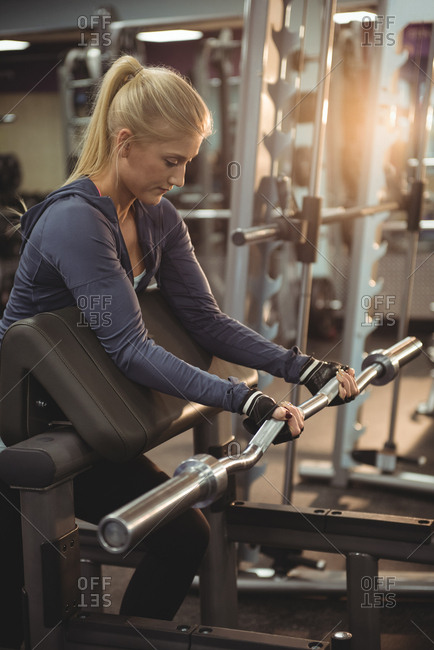 Fit woman exercising with curl bar in the gym
