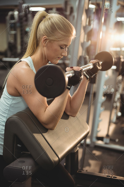 Fit woman exercising with barbell in the gym