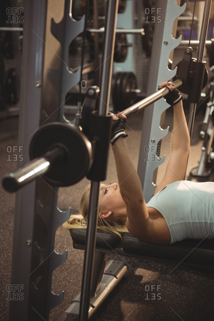 Fit woman exercising with smith machine in the gym