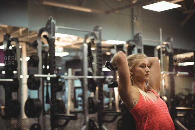 Fit woman exercising with a dumbbell in the gym