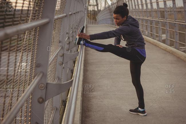 Full length of woman exercising on bridge