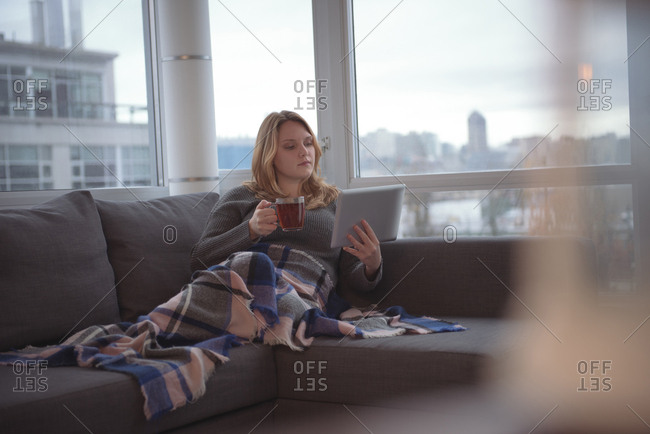 Woman using digital tablet while having coffee on sofa at home