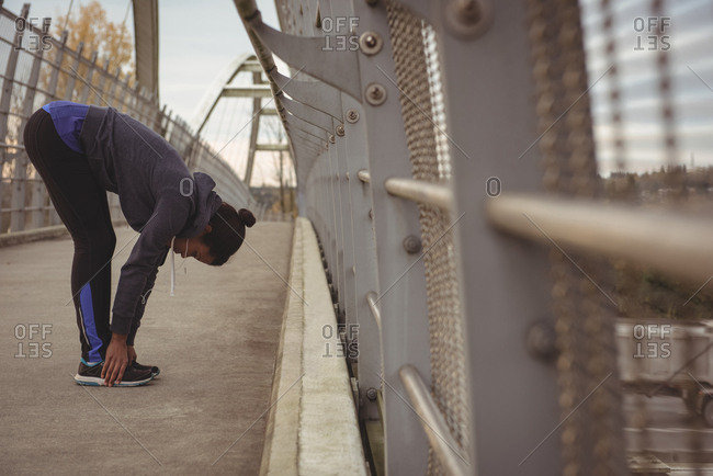 Full length of woman exercising by railing on bridge