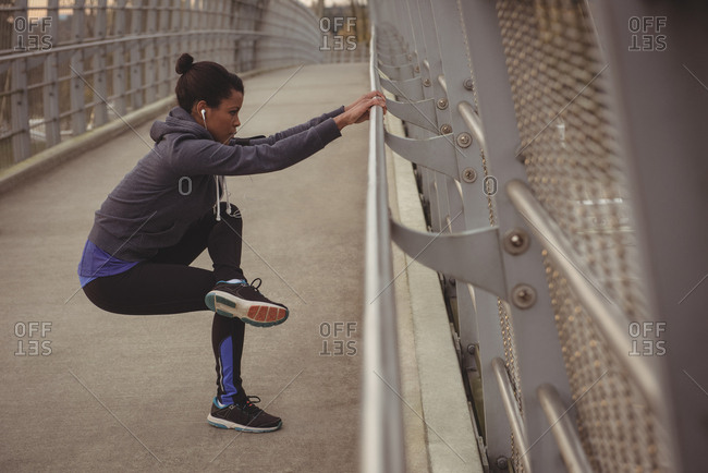 Side view of woman exercising by railing on bridge