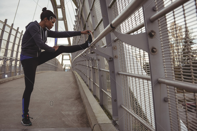 Side view of woman stretching legs on railing at bridge