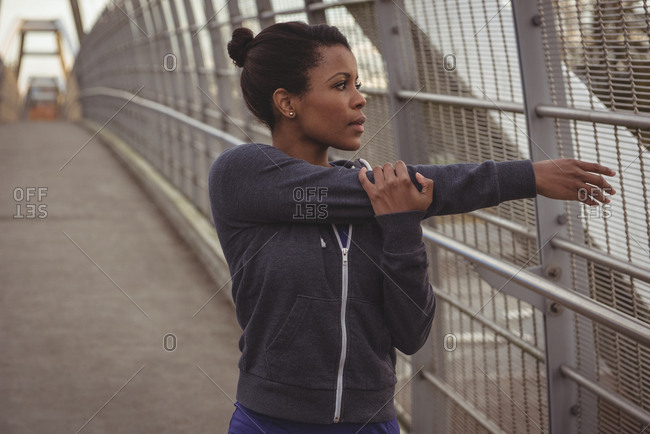 Woman looking away while stretching arms on bridge