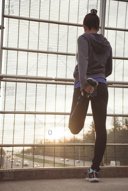 Full length of woman stretching legs on bridge