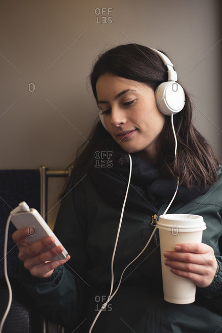Woman listening music on smart phone while holding coffee cup against wall