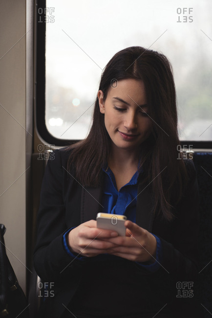 Woman using mobile phone while sitting by window in train