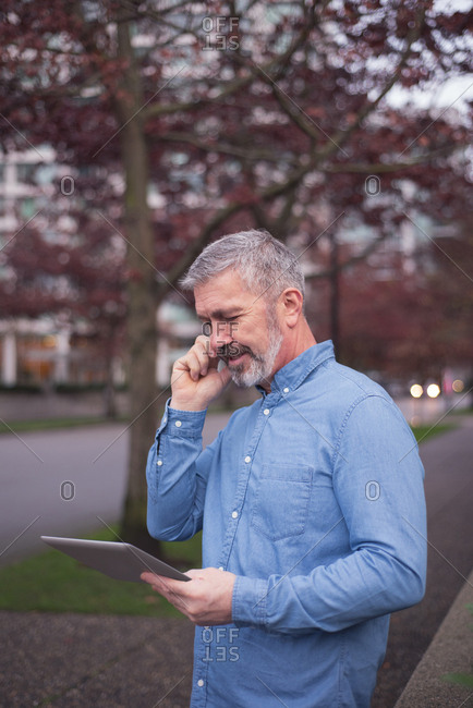 Businessman using smart phone and digital tablet while standing at park