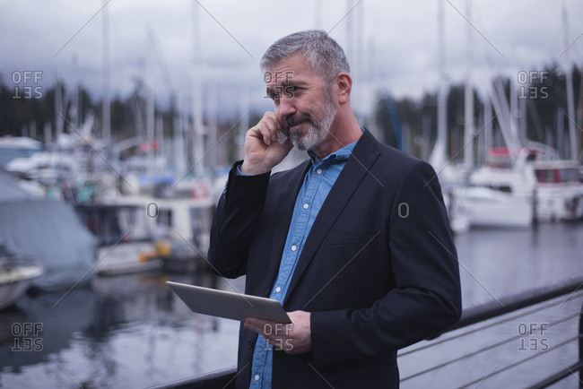 Businessman using smart phone while holding tablet PC by harbor