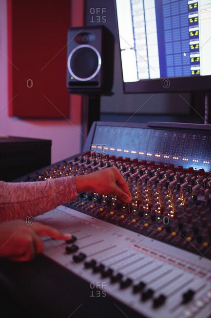 Hands of male audio engineer using sound mixer in recording studio