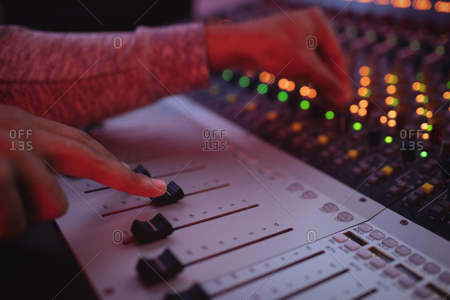 Hands of male audio engineer using sound mixer in recording studio