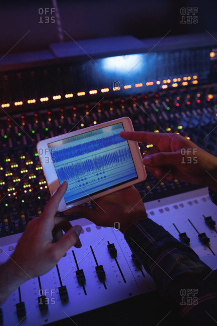 Male audio engineers using digital tablet in recording studio