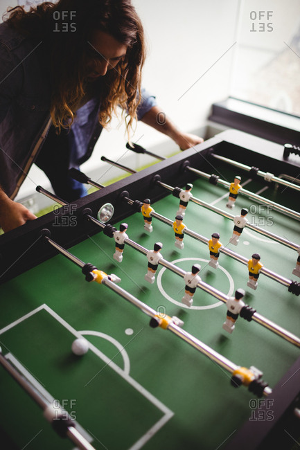 Concentrated man playing table football game