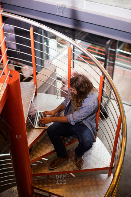 Sound engineer using laptop on stairs in office