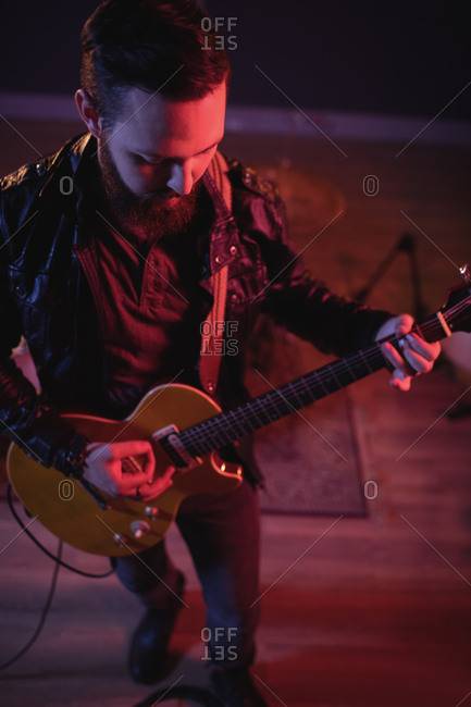 Close-up of guitarist playing electric guitar in recording studio