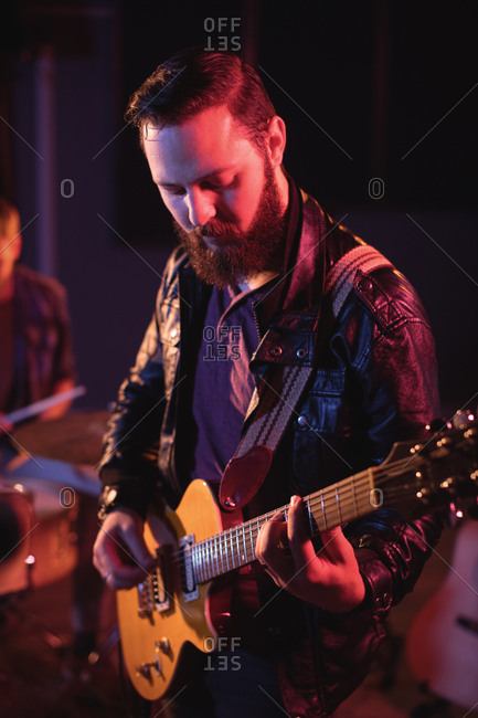 Musician playing electronic guitar in recording studio