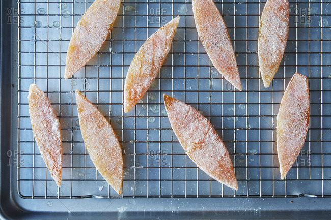 Candied citrus peels coated in sugar on cooling rack