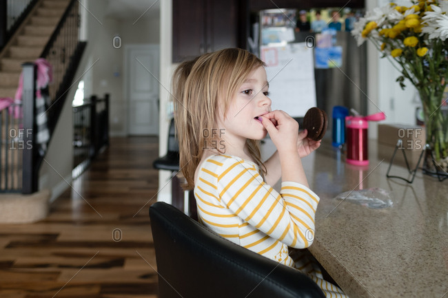 Girl with fingers in her mouth sitting at the counter and holding a cookie
