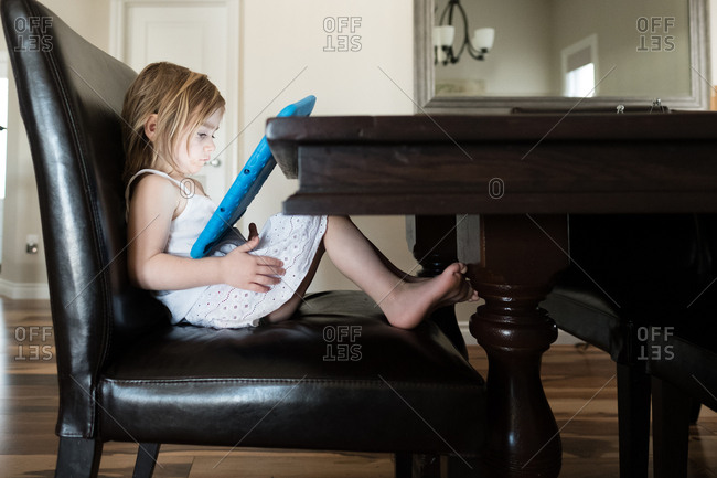 Girl sitting in chair watching digital tablet