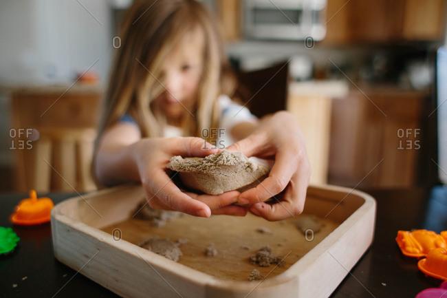 Boy holding sand clump in kitchen