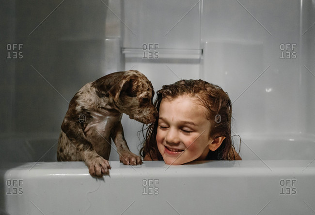 Dog and boy in bathtub together