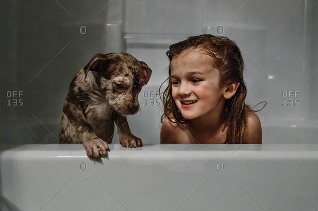 Dog and boy in a bathtub together