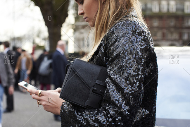 London, UK - February 20, 2017: Waist up view of woman using smartphone in street outside Christopher Kane fashion show, London Fashion Week, day four.