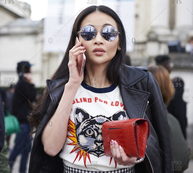 London, UK - February 20, 2017: Waist up view of woman wearing Gucci top and leather jacket, holding Hermes purse, using phone outside Christopher Kane fashion show, London Fashion Week, day four.