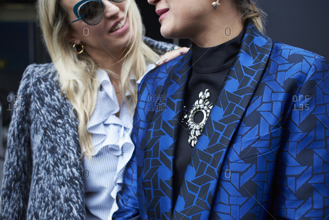 London, UK - February 21, 2017: Mid section close up of two fashionable women, one wearing a wool jacket and the other a patterned silk jacket, London Fashion Week, day five.