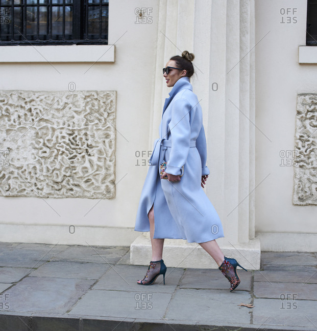 London, UK - February 20, 2017: Full length view of woman in pale blue coat and high heels walking in city street, London Fashion Week, day four.