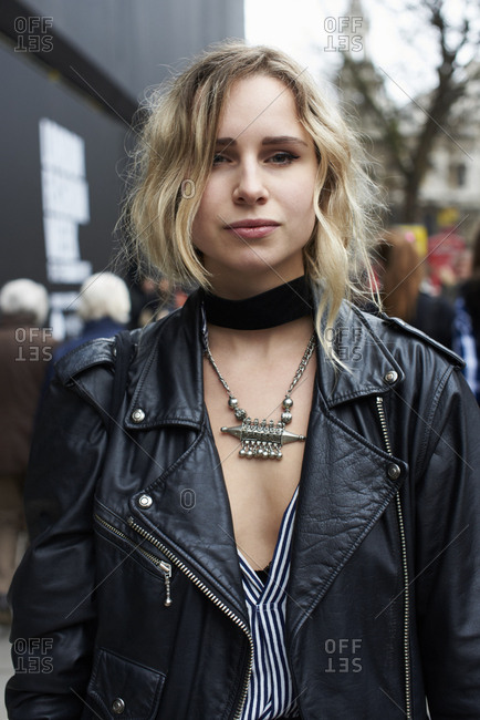London, UK - February 21, 2017: Waist up view of woman wearing a black leather jacket, black choker and a silver tribal necklace in the street, London Fashion Week, day five.