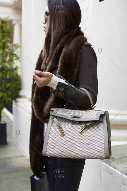 London, UK - February 21, 2017: Three quarter length view of woman standing in the street holding a Hermes handbag, London Fashion Week, day five.